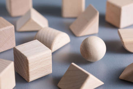 Closeup one wooden sphere ball in the group of geometry wood blocks, find your niche concept 版權商用圖片