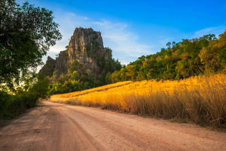 Beautiful limestone mountain and field at sunset on the dirt road in countryside, Noen Maprang, Phitsanulok, Thailand
