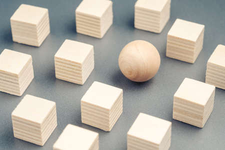 Wooden sphere ball among the wood cubes, different and position in niche market concept