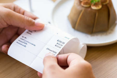 Closeup hand holding food bill to check the price with cake on background
