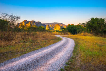Gravel road on the field to the limestone mountain in sunlight, travel at Noen Maprang, Phitsanulok, Central of Thailand