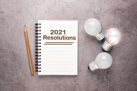 Opened small notebook with text : 2021 Resolutions, and glowing light bulbs as planning idea