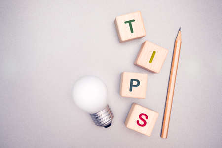 Tips concept on wooden cubes with light bulb and pencil on gray background
