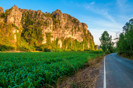 Limestone mountain range and sugar cane farm along the country road, beautiful countryside and tourist attraction at Noen Maprang district, Phitsanulok, Thailand