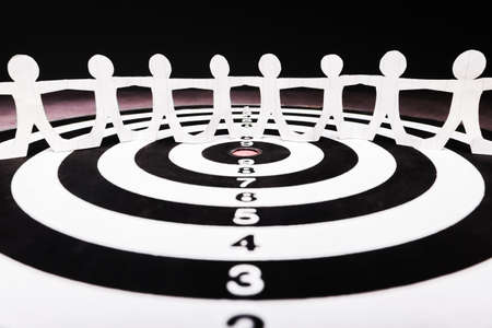 Paper human chain on target dartboard, human join together for one purpose, team and goal setting Stock Photo