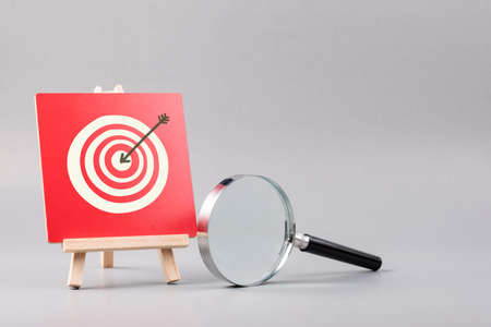 Magnifying glass and target accuracy on wood sign, business plan and marketing strategy, target customer concept 版權商用圖片