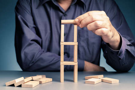 Man build a ladder tower with wooden domino toy,  going to add another piece on the base and risk to make it all down, risk assessment, risk management concept