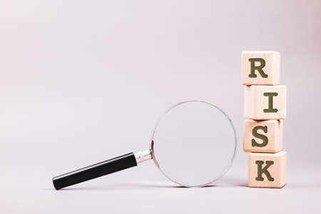 Wood blocks with text RISK and magnifying glass, risk assessment concept