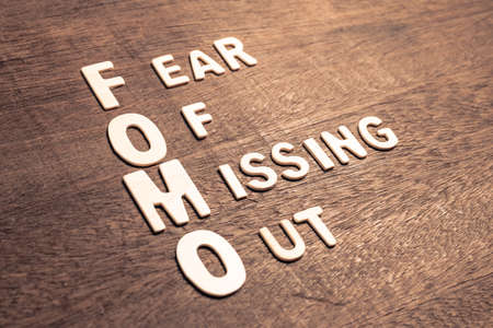 FOMO abbreviation or Fear of Missing Out arranged by wood letters on wood background, FOMO marketing
