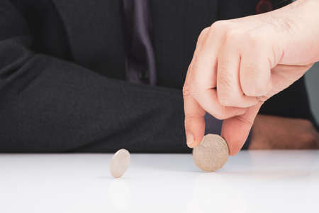 Closeup businessman gamble by spinning the coin on the table, decision situation