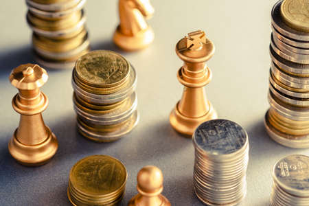 Closeup king chess in the group of money coins heap. Financial game strategy, financial planning. Business competition concept 版權商用圖片