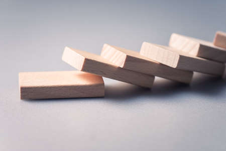 Closeup wooden piece of domino falling down in a row, domino effect concept