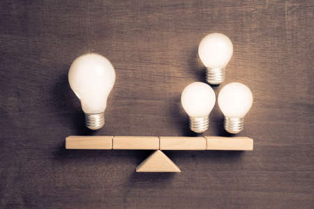 Big and small light bulbs on scale symbol, group of small light bulbs have equivalent weight as big light bulb, business size concept