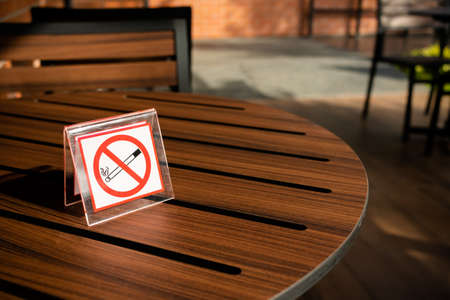 No smoking sign on the wood table at outdoor zone in the cafe
