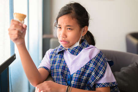 Student girl have a hypersensitive teeth while eating ice-cream in the cafe after school 版權商用圖片