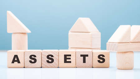 ASSETS wood blocks with wooden toy on the table, financial accounting, owned business resources concept 版權商用圖片