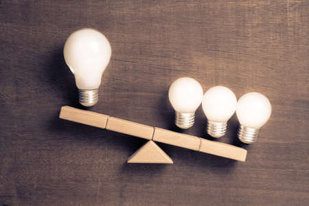 Big and small light bulbs on scale symbol, group of small light bulbs have more weight than a lone big light bulb, business size or teamwork concept