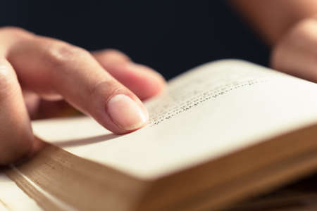 Closeup index finger place at the sentence in the old book to repeat the point of content while reading the novel