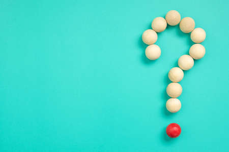 Many small wood balls arranged as question mark sign on green background
