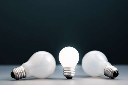Small light bulb is standing and glowing while the big ones was laying down, advantage of small thing,  small business in competition idea, find a niche business 版權商用圖片