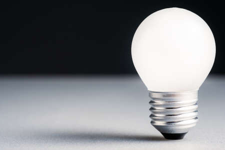 Closeup shot of small white light bulb glowing, original idea, knowledge and power, startup business, find a niche concept