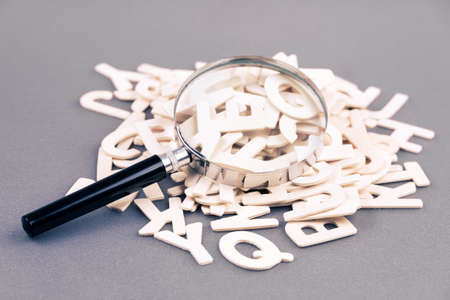 Magnifying glass on a pile of wooden alphabets