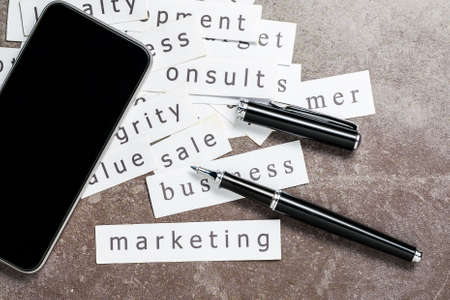 Marketing, and kind of business word printed on the paper, scattered on the table with pen and smart phone, marketing topic and concept