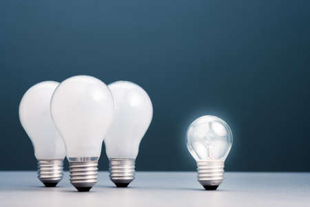 Small light bulb has own light and more brighter than the group of big ones, small business in competition idea, coaching or success training concept 版權商用圖片