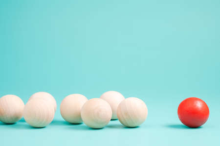 Different small red ball in the group of wooden balls on green background, leader or influencer with follower, branding and marketing concept