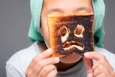 Child girl with towel on her head after bath show the scared icon face on the burnt toast, funny moment of mistake, danger of charred food concept
