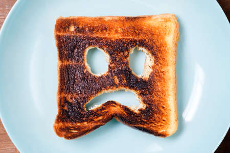 Burnt toast with sad face icon on the green plate, concept for charred food or the bad day start at the early morning 版權商用圖片