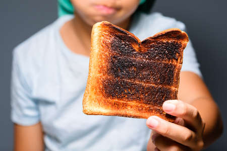 Closeup child girl show the burnt toast to the camera, danger of charred food concept