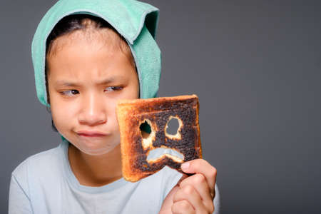 Child girl wih towel on her head after bath not sure whether to eat the burnt toast that has a scared face icon on it, danger of charred food, funny moment of mistake 版權商用圖片