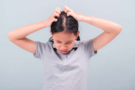 Child girl feel itchy at her head and try to scatch the hair