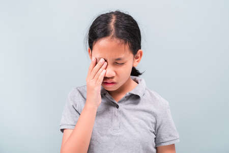Eleven years old girl has a problem with her eye and use the hand to touch and cover it