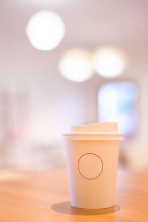 White take away coffee cup with cap on the table, shallow depth of field to blur background