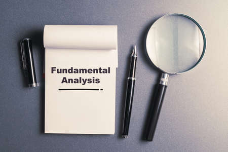Fundamental Analysis text on small notepad with pen and magnifying glass