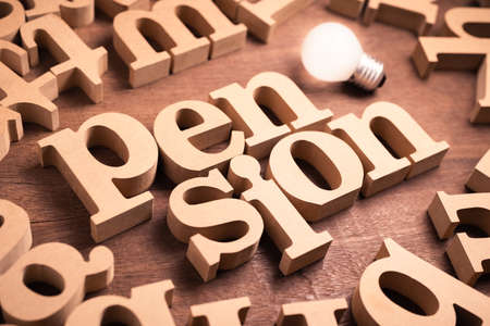 Pension word in scattered wood alphabets on the table with glowing light bulb