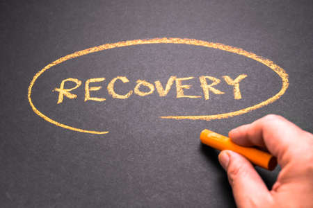 Closeup hand write a RECOVERY word topic on chalkboard, business recovery plan concept