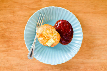 Scones bread with butter and strawberry jam on green plate