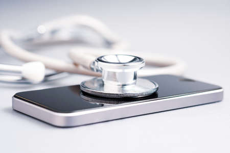 Closeup stethoscope placed on smart phone on the table, medical online service, telehealth, 版權商用圖片