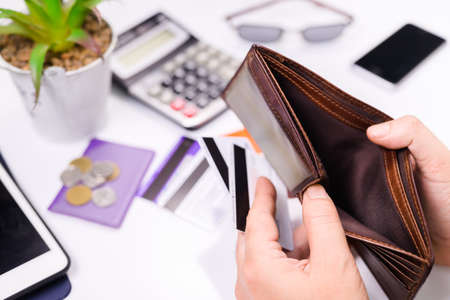 Closeup hand open the empty wallet with some credit cards in hand and placed on the desk, credit card debt