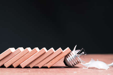 Domino effect falling down and shatter the small light bulb 写真素材