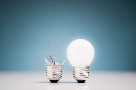 Broken and glowing light bulb in comparison