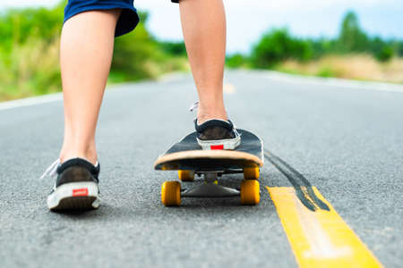 Closeup legs of child girl playing skateboard on the ashalt road around the nature in countryside