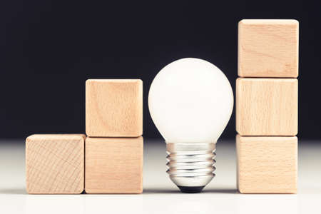 Small wood blocks built as step stairs symbol with small light bulb as connection of progress or helpful idea support to success 写真素材