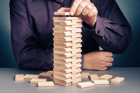 Businessman playing wood blocks toy by building as a high tower, making project to success