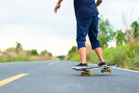 Closeup legs of child girl playing skateboard on the asphalt road around the nature in countryside