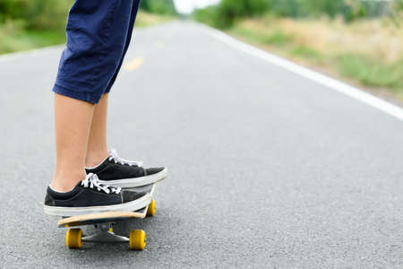 Closeup legs of child girl playing skateboard on the asphalt road