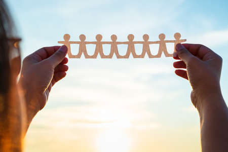 Closeup woman's hands unfold the paper human chain over the sunset sky